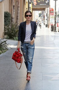 Rachel Bilson flashes a smile as she struts down Hollywood Blvd in ripped baggy jeans and clogs, and a navy blazer